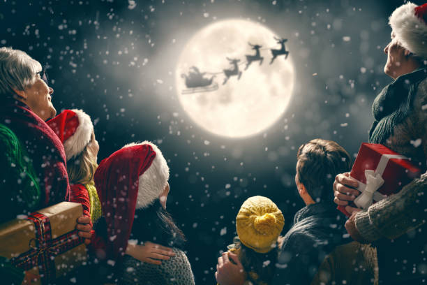 Family enjoying Christmas Merry Christmas and happy holidays! Cute little children with mom, dad, grandma and grandpa. Santa Claus flying in his sleigh against moon sky. Family enjoying the holiday on dark background. sleigh stock pictures, royalty-free photos & images