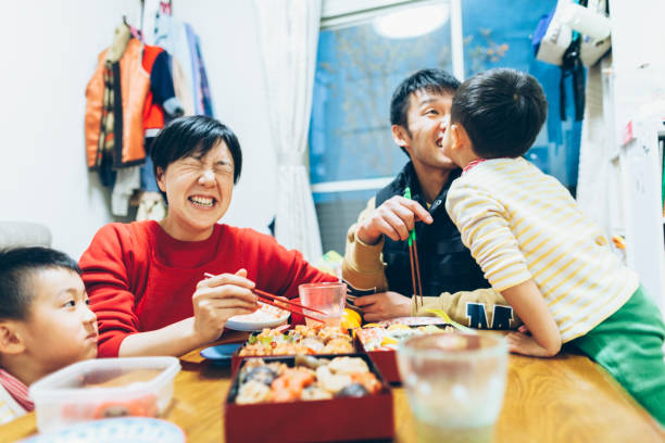 家族一緒に食事を楽しんで - 家族 日本人 ストックフォトと画像