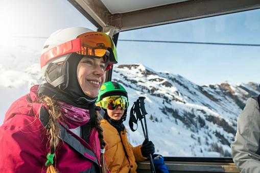 Family enjoying gondola ski lift ride in Alps