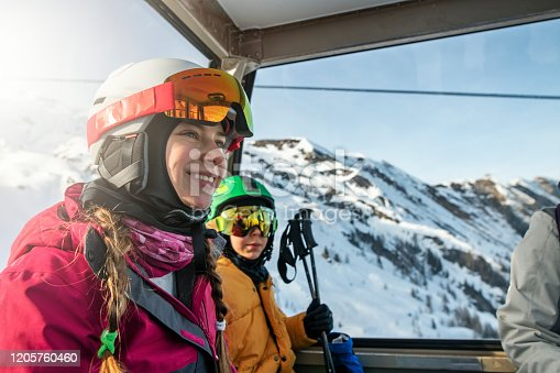 Teenage girl with her family skiing at alpine glacier on a sunny winter day. Family is sitting in ski lift gondola and enjoying the views. Nikon D850