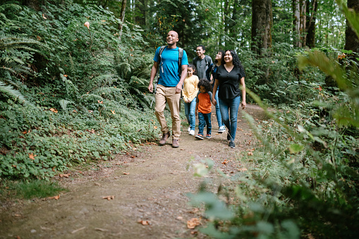 A young mixed race family spends time together outside in Washington state, enjoying the beauty of the woods in the PNW.