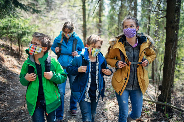 Family enjoying hiking in forest during the COVID-19 pandemic stock photo