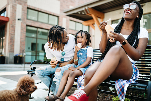A cute young African American family enjoys relaxation time in the city of Tacoma, Washington with ice cream cones on a hot summer day.  Their poodle dog waits for them to finish.