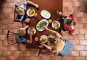 Overhead shot of mother and kids having pasta and fried vegetables for lunch. Nikon D850