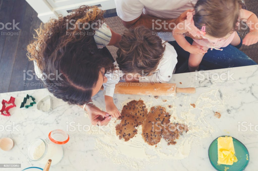 Family enjoying making cookies together. stock photo