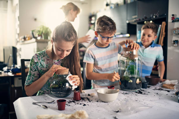 Family enjoying making plant bottle gardens Kids having fun creating bottle gardens at home. They are potting little plants inside bottles to create miniature living eco-systems and beautiful home decoration. Nikon D850 recreational pursuit stock pictures, royalty-free photos & images