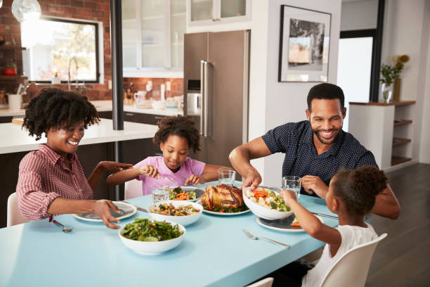 family enjoying meal around table at home together - family dinner stock photos and pictures