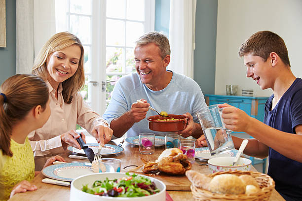 family enjoying meal at home together - family dinner stock photos and pictures