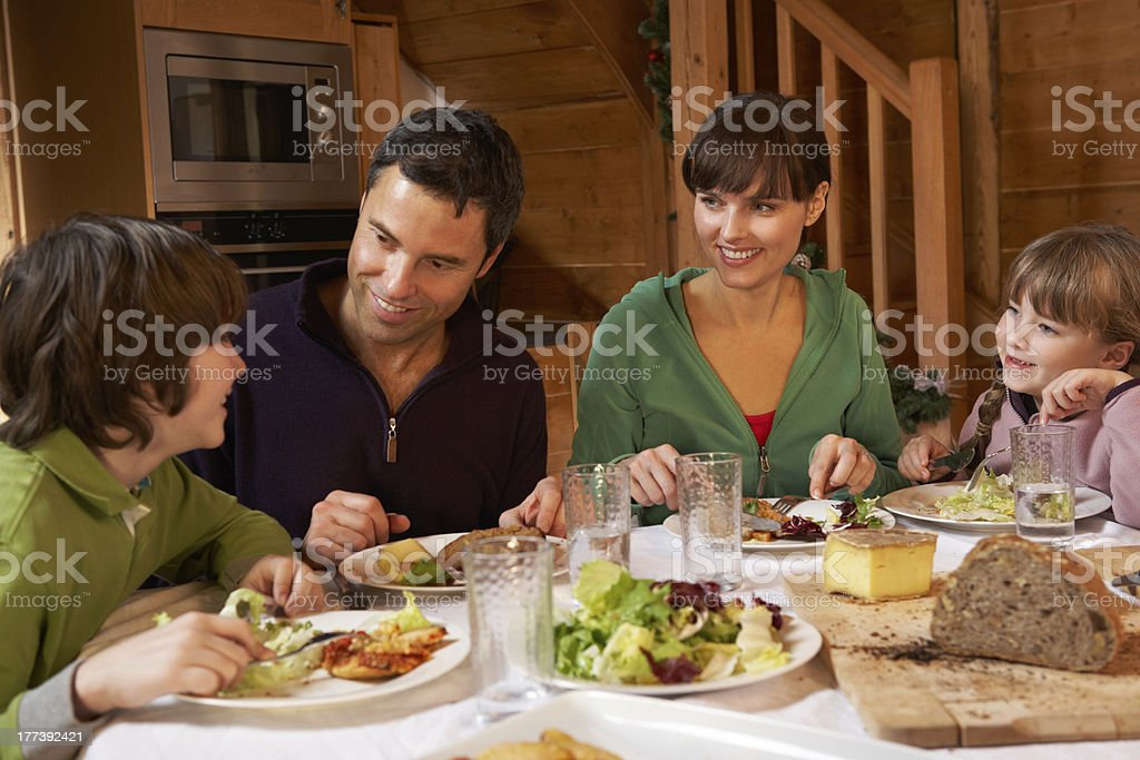 Family Enjoying Meal In Alpine Chalet Together stock photo