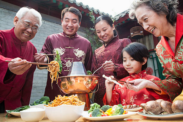 Family enjoying meal in traditional Chinese clothing stock photo