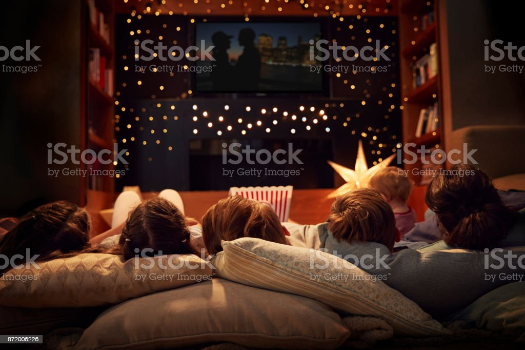Family Enjoying Movie Night At Home Together stock photo