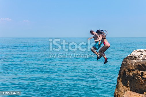 Father and daughter enjoying on summer vacations in Greece. They jumping together from cliff and diving into blue sea