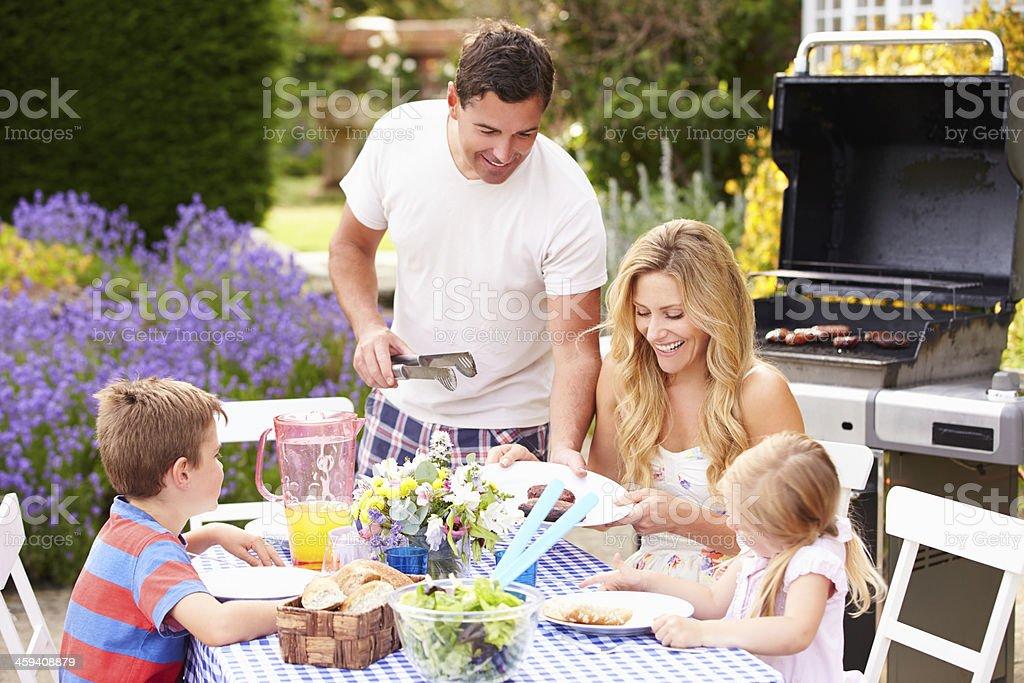 Famille appréciant un barbecue dans le jardin - Photo