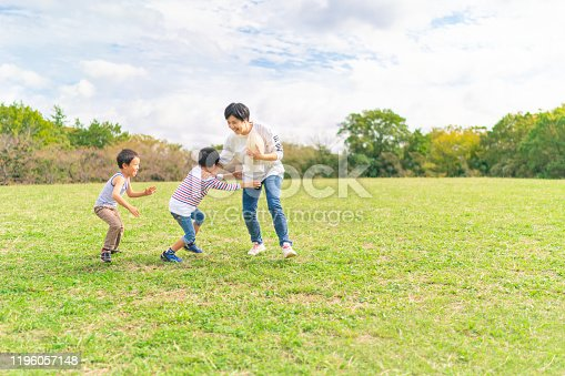 589135214 istock photo Family enjoying playing rugby in public park 1196057148