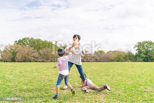 589135214 istock photo Family enjoying playing rugby in public park 1199460910