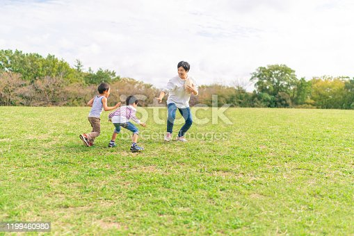 589135214 istock photo Family enjoying playing rugby in public park 1199460980