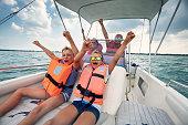 Family enjoying Garda Lake vacations. Parents and kids riding a boat on Lake Garda.\nNikon D850