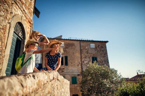 family enjoying sightseeing small italian town - europe travel stock photos and pictures