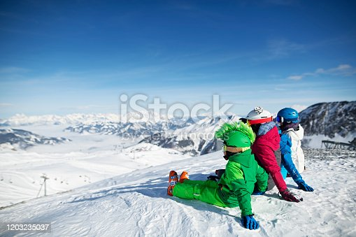 Mother with kids are skiing together down at glacier in the Alps. Sunny winter day. The  family is looking at the spectacular view. Nikon D850