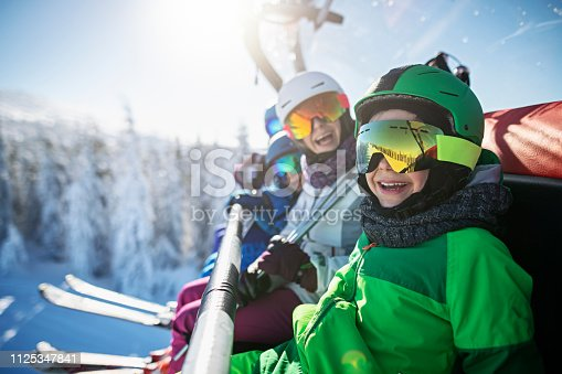 Mother skiing with kids on a sunny winter day. Family is sitting on chairlift cheering at the camera. Nikon D850