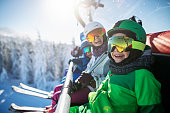 Mother skiing with kids on a sunny winter day. Family is sitting on chairlift cheering at the camera.\nNikon D850