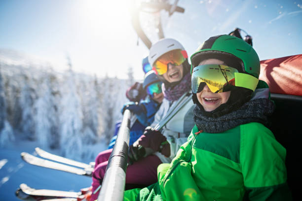 Family enjoying skiing on sunny winter day Mother skiing with kids on a sunny winter day. Family is sitting on chairlift cheering at the camera. Nikon D850 ski stock pictures, royalty-free photos & images