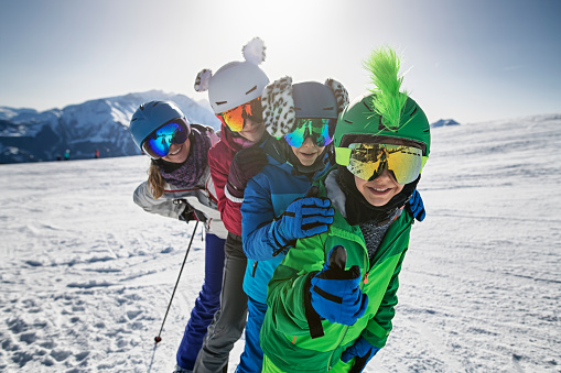 Family is skiing together down at glacier in the Alps. Mother and kids enjoy spending time skiing together. Sunny winter day. Nikon D850