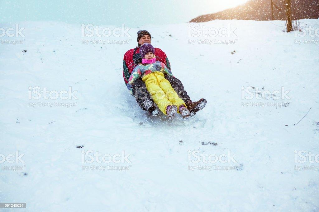 Family enjoying sledge ride stock photo