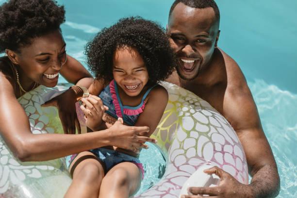 Family enjoying summer holidays in pool stock photo