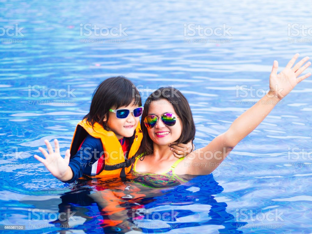 Family enjoying summer vacation in luxury swimming pool foto de stock royalty-free