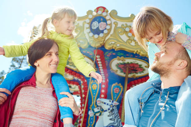 Family enjoying sunny day in funfair stock photo
