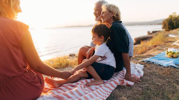 familie bei sonnenuntergang - griechische partyspeisen stock-fotos und bilder