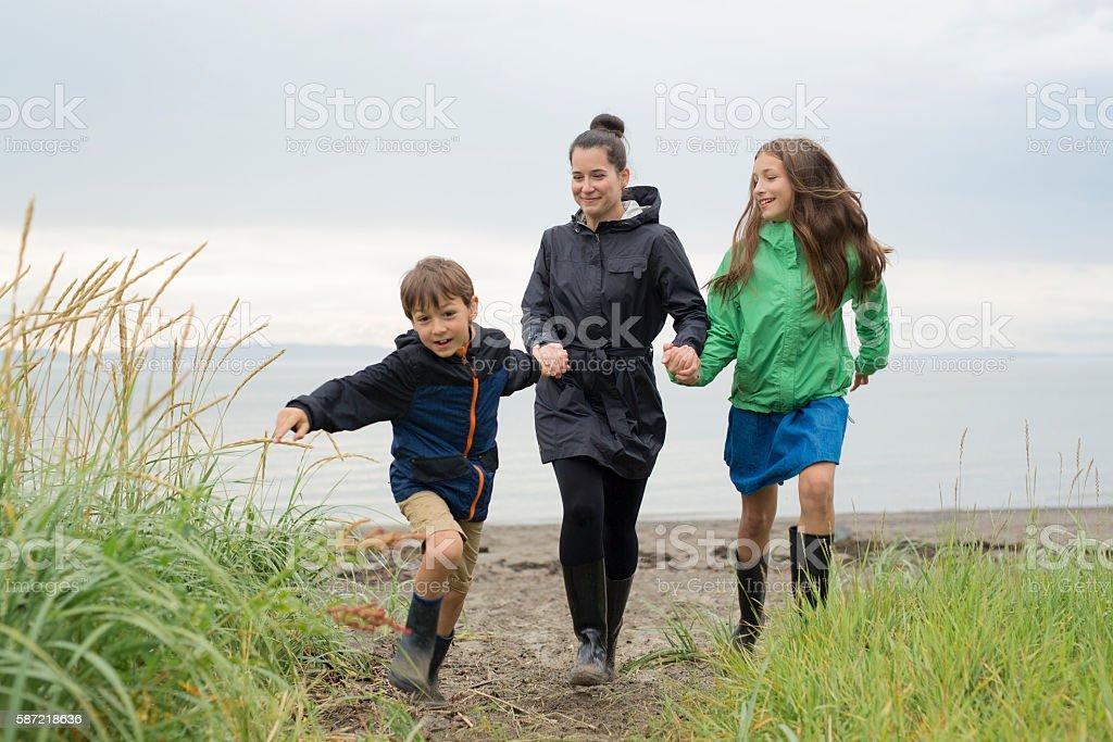 Family enjoying the rain and having fun outside on the stock photo
