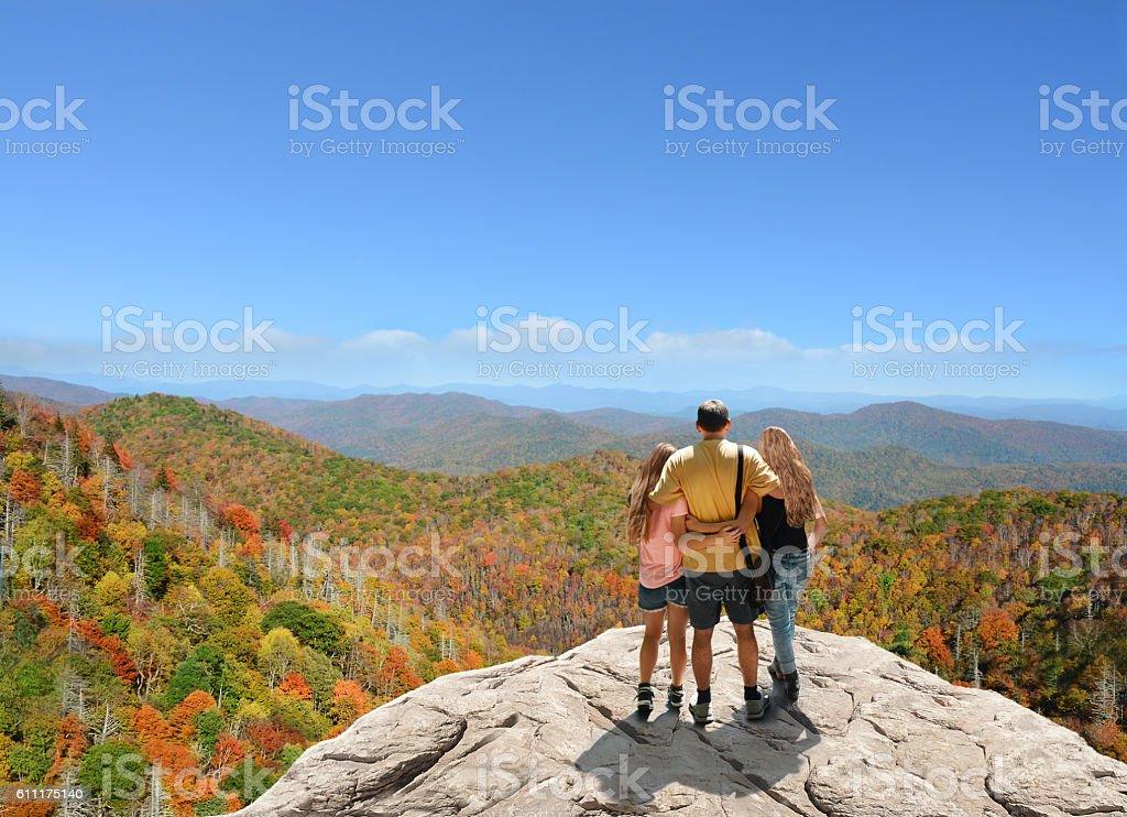 Family enjoying time on the top of mountain. stock photo