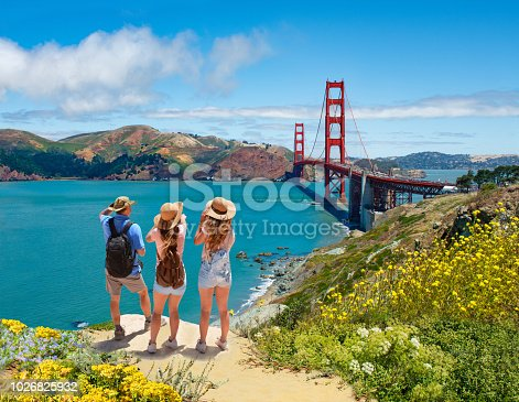 People enjoying time together on vacation hiking trip.  Golden Gate Bridge, over Pacific Ocean, mountains in the background. San Francisco, California, USA