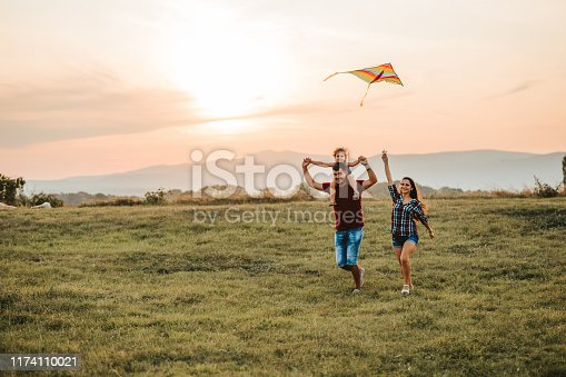Young caucasian parents and their daughter running on a meadow with kite. Father carrying daughter on his shoulders.