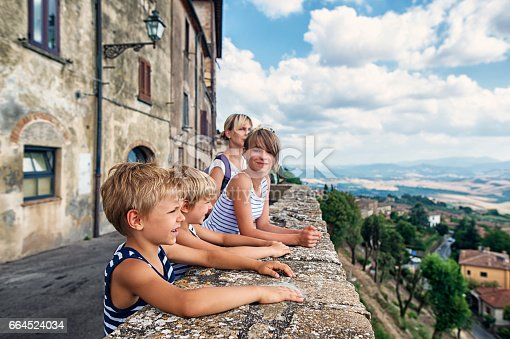 Mother and kids tourists sightseeing beautiful Italian town of Volterra. Family is admiring view from terrace.