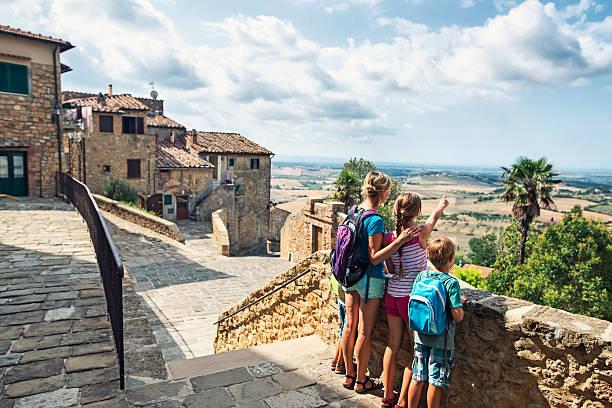 family enjoying view in little italian town in tuscany - toskana ferien stock-fotos und bilder