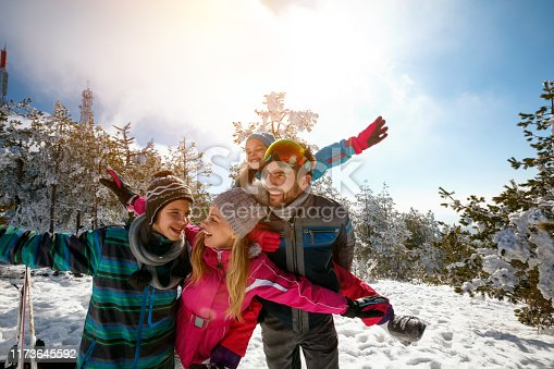 Happy family with children on winter ski vacationHappy family enjoying winter vacations in mountains and making selfie