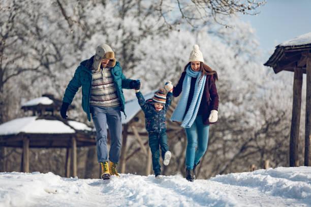 familie winter-spaziergang im wald. - gute winterjacken stock-fotos und bilder