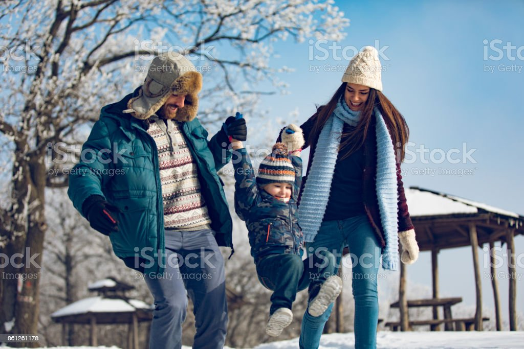 Family enjoying winter walk in the forest. stock photo