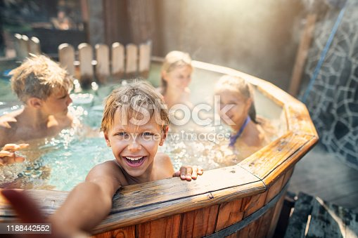 Family is playing in wood fired barrel hot tub in the back yard. Boy is laughing at reaching at the camera. Nikon D850