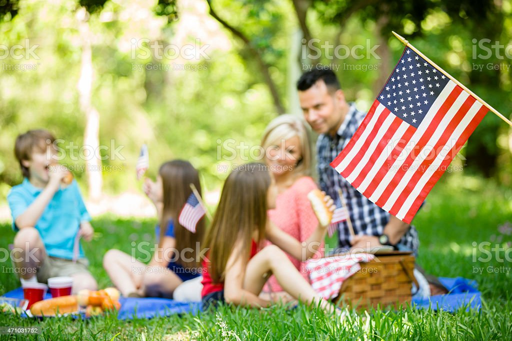 Family enjoys July 4th picnic in summer season. American flag. stock photo