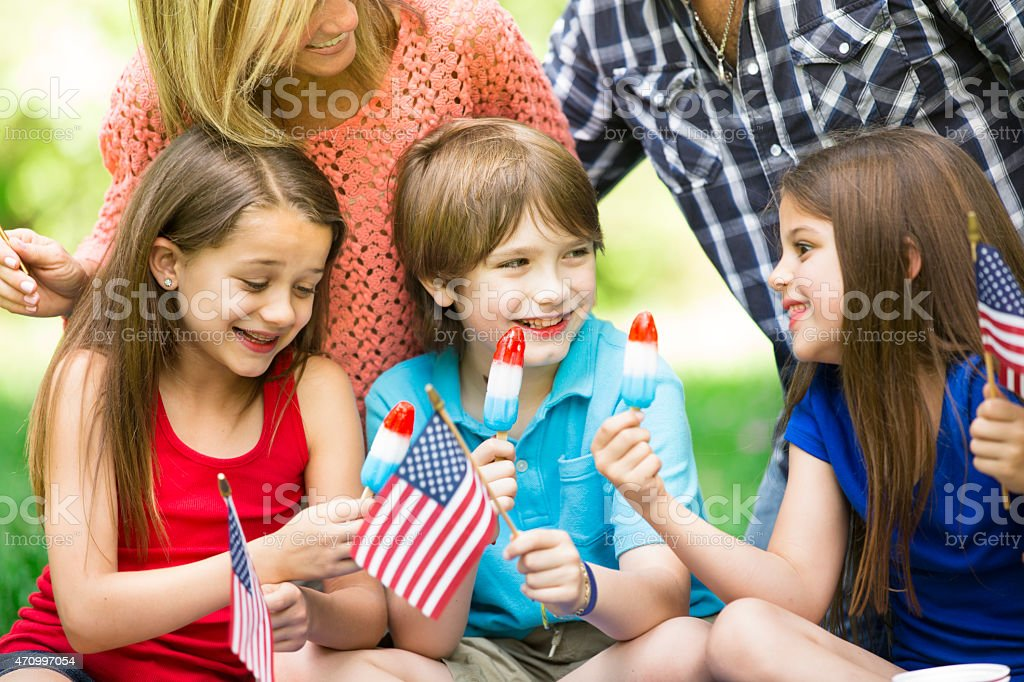 Family enjoys July 4th picnic in summer season. American flags. stock photo