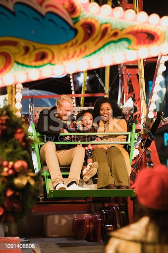 A front-view shot of a mother and father with their young daughter having fun on a Ferris wheel at an amusement park, the young girl's grandmother watches on from the ground.