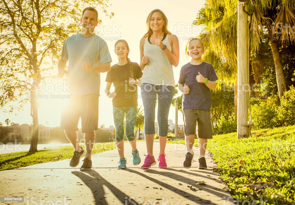 Family exercising and jogging together at the park stock photo