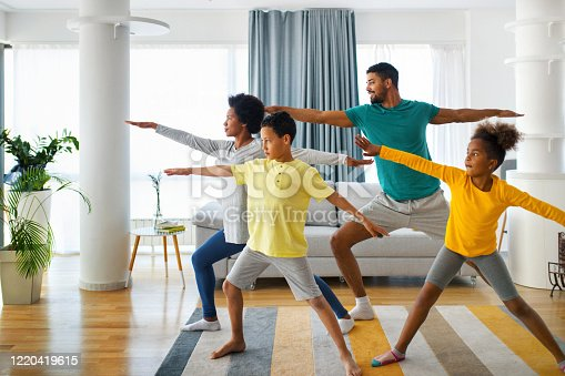 Closeup front view of a young african american family with son and daughter exercising at home during coronavirus quarantine. They are practicing some yoga moves.