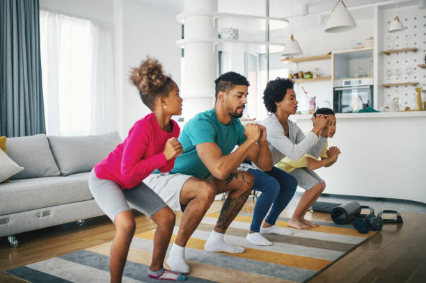 Family exercising at home stock photo