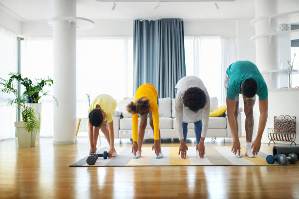 Family exercising yoga at home Closeup front view of a young african american family with son and daughter exercising at home during coronavirus quarantine. They are stretching by touching their toes. touching toes stock pictures, royalty-free photos & images