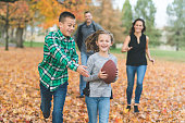 A young girl races toward the camera with a big grin and.full-size football. Her big brother is about to catch up and grab it from her - or tackle her - and their parents are chasing them both down just a short ways behind. All of them are smiling as they run through the autumn leaves.